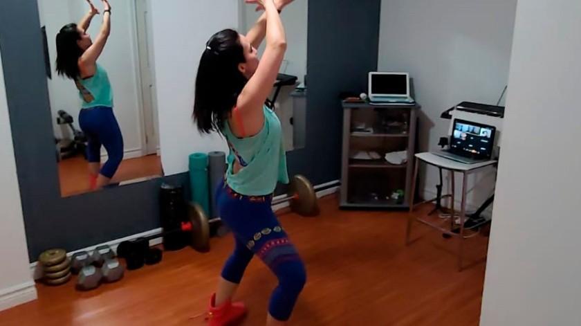 La instructora Angela Correa da una clase virtual de Zumba desde su apartamento en Toronto, Canadá.(AP)