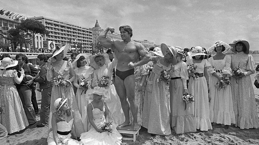 """Arnold Schwarzenegger, cuyo documental """"Pumping Iron"""" se estrenaba en el Festival de Cine de Cannes, hace alarde de sus músculos en una playa en Cannes, Francia.(AP)"""