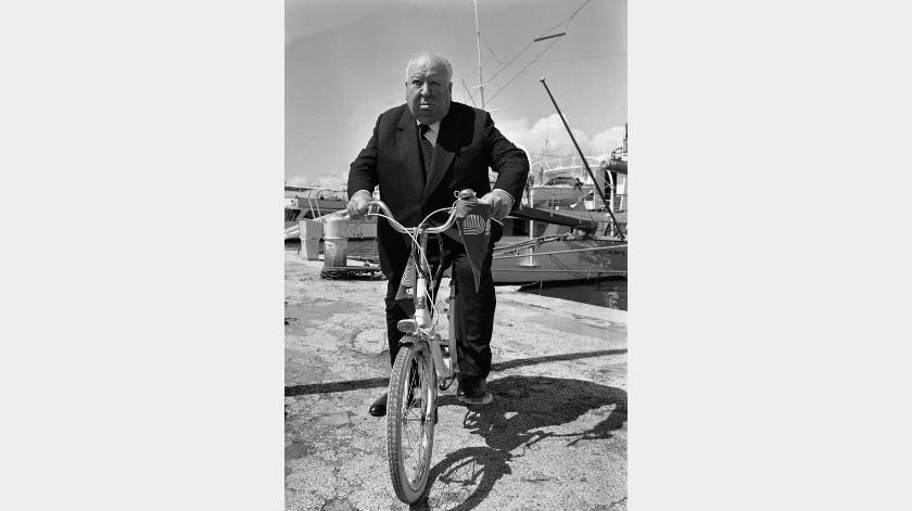 El maestro del cine de suspenso Alfred Hitchcock pedalea al Festival de Cine de Cannes, en Cannes, Francia.(AP)