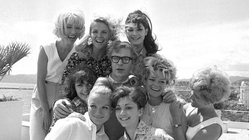 """El actor Michael Caine posa con un grupo de chicas tras dar una conferencia de prensa en la azotea del Palacio del Festival, durante el Festival de Cine de Cannes, en Cannes, Francia. Estaba promocionando su pelÁ¡cula """"Alfie"""", que terminó recibiendo el premio especial del jurado.(AP)"""