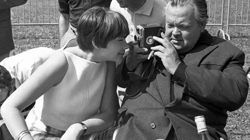 La actriz Macha Meril se asoma por el lente de la cámara mientras es filmada por Orson Welles durante una fiesta en el Festival de Cine de Cannes en el Club de Golf Mandelieu, en Cannes, Francia.(AP)