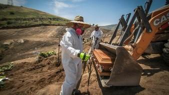 Trabajadores con equipo de protección descargan un ataúd con los restos de una persona que murió por coronavirus, en una apartada área del cementerio municipal destinada para víctimas de Covid-19, en Tijuana.