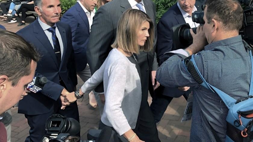 En esta fotografía de archivo del 27 de agosto de 2019 Lori Loughlin sale de una corte federal con su esposo el diseñador Mossimo Giannulli, izquierda, en Boston.(AP)