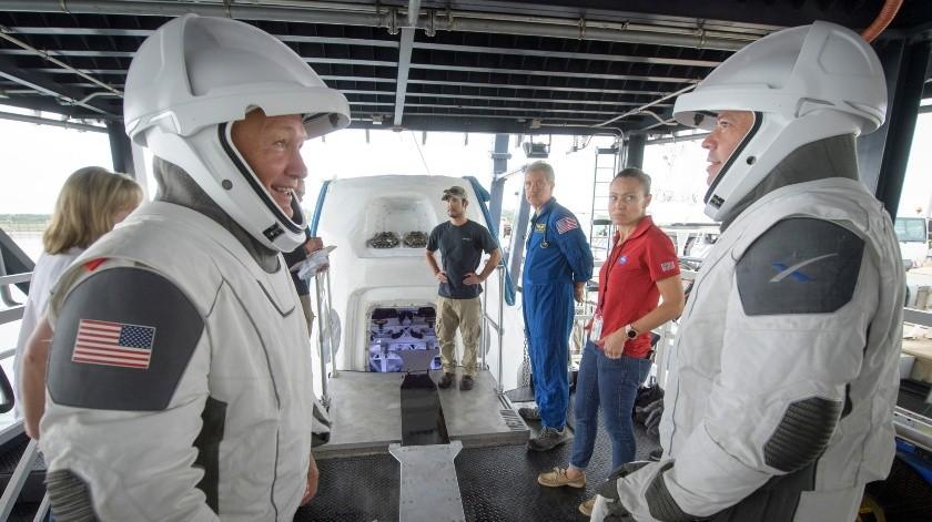 En esta foto de archivo del 13 de agosto de 2019, los astronautas de la NASA Doug Hurley, izquierda, y Bob Behnken junto con equipos de la agencia espacial y la empresa SpaceX ensayan cómo salir de la cápsula Crew Dragon que transportará a seres humanos a la Estación Espacial Internacional, en Cabo Cañaveral, Florida.(AP, NASA)