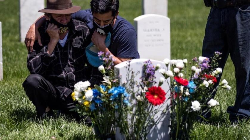 Salomón  y César usan mascarillas mientras visitan la tumba de su hijo y hermano respectivamente, en el Cementerio Nacional de Los Ángeles durante el Memorial Day.(EFE)