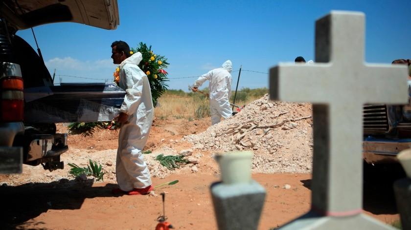 Un trabajador de una funeraria baja un ataúd con una víctima de COVID-19.(EFE, EFE)