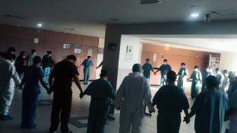 Médicos y enfermeras elevan una oración antes de iniciar su labor diarira.