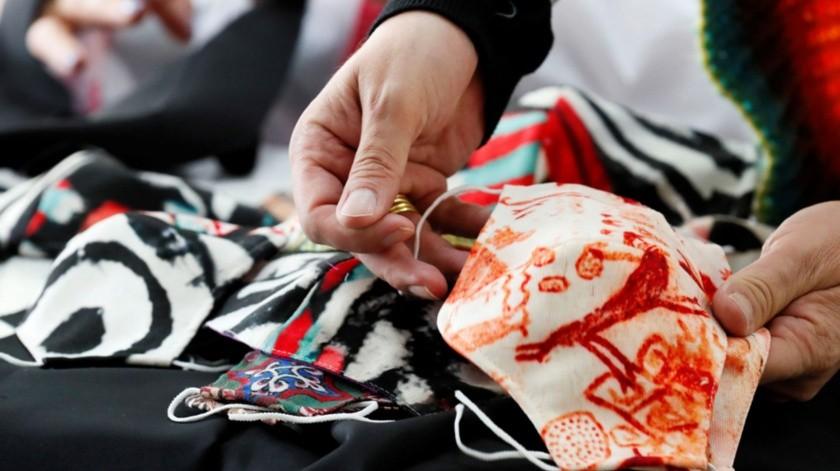 Mascarillas creadas por el diseñador colombiano Diego Guarnizo para su nueva colección de ropa con tela estampada antifluidos en Bogotá.(EFE)