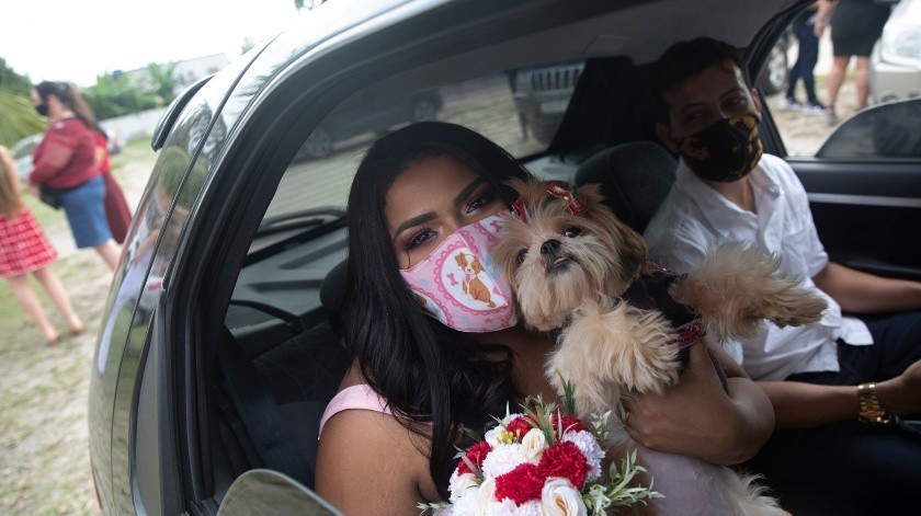 Con mascarillas para protegerse del coronavirus, Erica da Conceiçao y Joao Blank se sientan en el asiento trasero de un auto para una boda en un drive-thru en el registro del vecindario de Santa Cruz, en Río de Janeiro, Brasil, el 28 de mayo de 2020. Un notario presidió la ceremonia desde el exterior. No fue el acto romántico que la pareja había imaginado, pero era una de sus pocas opciones en plena pandemia del COVID-19.(Copyright 2020 The Associated Press. All rights reserved., AP)