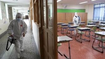Trabajadores con equipos de protección desinfectan un aula en un centro de educación secundaria durante la pandemia del coronavirus, en Busan, Corea del Sur.