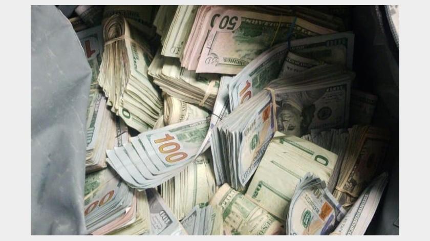 Las autoridades encontraron que entre los asientos había una mochila con diversos fajos de billetes americanos.