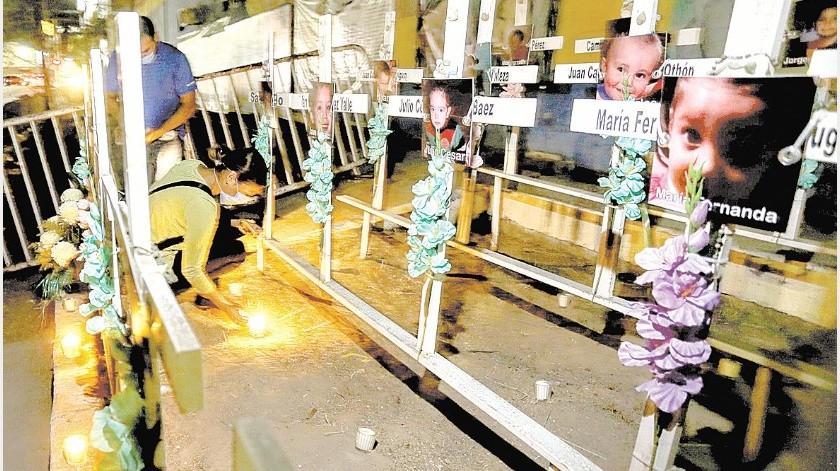 Un grupo de padres de niños que perdieron la vida en el incendio de la guardería ABC, colocó veladoras en las cruces que tienen los retratos de los 49 niños que allí murieron hace ya once años.(Eleazar Escobar)