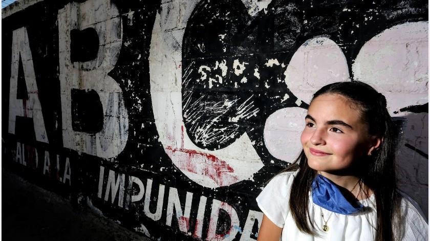 Alexia se resguarda del Sol en una pared que tiene un rótulo, donde se exige justicia para las víctimas del incendio ABC.(Especial)