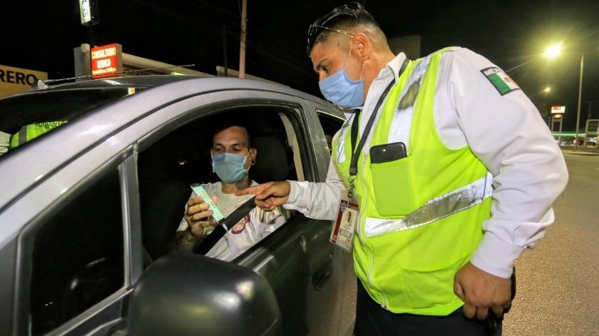 El conductor de un vehículo muestra el permiso de tránsito para circular fuera del horario establecido por la autoridad.(Eleazar Escobar)