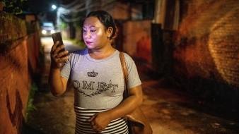 Sunita Lama, una trabajadora transexual, mira su teléfono en una calle de Katmandú.