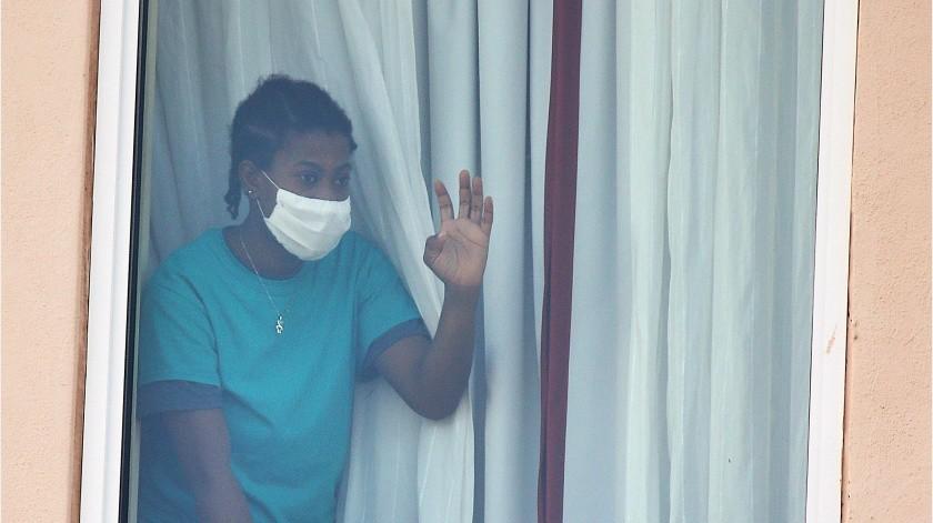 Una niña saluda desde una ventana mientras manifestantes agitan pancartas frente al hotel Hampton Inn el jueves 23 de julio de 2020, en McAllen, Texas.(AP)