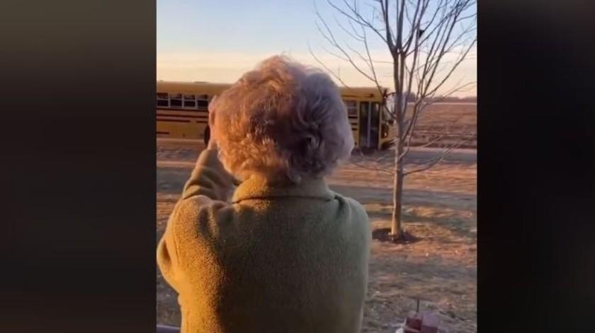 Una bella mujer se levanta todas las mañanas a saludar el autobús escolar