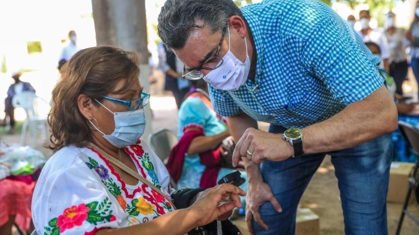 El secretario de Salud, Enrique Clausen Iberri, le explica a una mujer indígena cómo funciona el oxímetro.(EL IMPARCIAL)