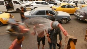 La gente se refresca del calor del verano en una ducha pública de Bagdad (Irak), donde las temperaturas han superado los 50 grados.
