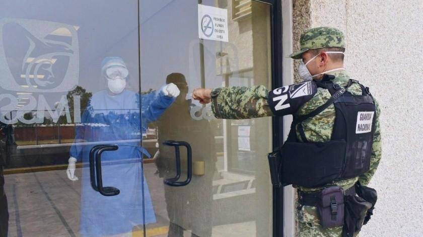 Un elemento de la Guardia Nacional saluda a una doctora que atiende a pacientes de Covid-19.(GH)