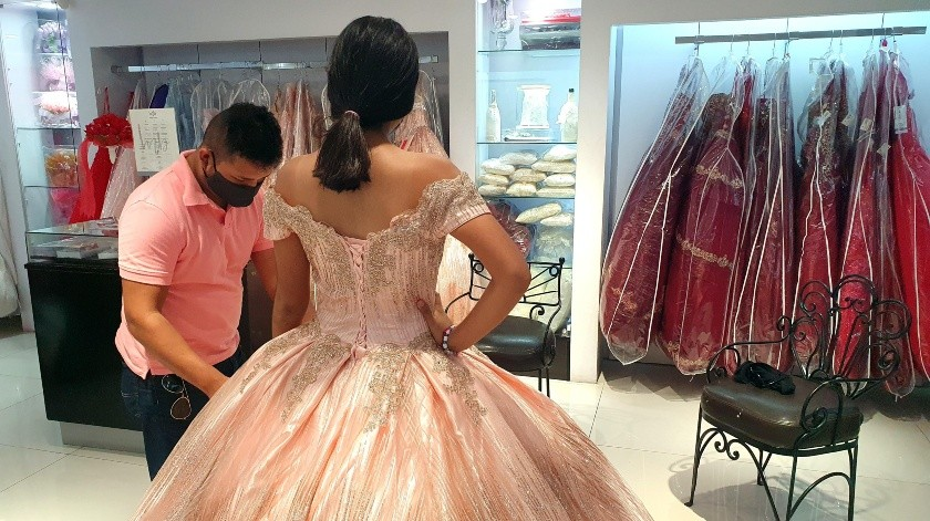 Una joven acompañada de sus padres acude a medirse vestido de 15 años en un comercio del Centro de Hermosillo, Sonora al reabrir ayer negocios no escenciales.(Julián Ortega)