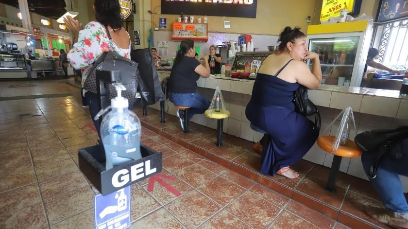 En los puestos de comida del Mercado Municipal colocaron botellas o jabas para que se respete la sana distancia y ofrecen gel en la entrada.(Anahí Velásquez)