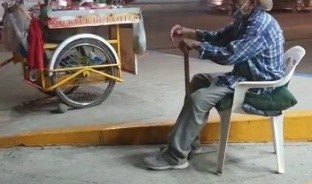 Don Joaquín Mendívil llega todos los días a las 6 de tarde a la esquina donde pone su triciclo en Navojoa, esperanzado en que a pesar de la pandemia, sus clientes volverán a comprarle elotes cocidos o en coctel, porque saben que trabaja para ganarse la vida.