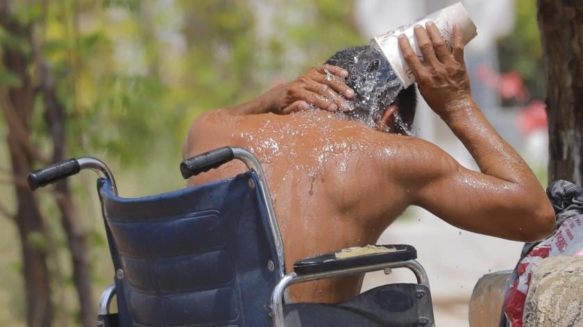 Un hombre en situación de calle se refresca echándose agua encima.(Julián Ortega)