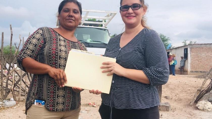 La señora Petra Palma recibe de manos de la maestra Gisela Mendívil (der.) cuadernos de tareas para sus hijos en la comunidad de Cucajaqui en el municipio de Álamos.(Cortesía)