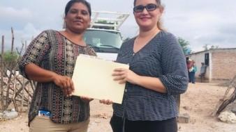 La señora Petra Palma recibe de manos de la maestra Gisela Mendívil (der.) cuadernos de tareas para sus hijos en la comunidad de Cucajaqui en el municipio de Álamos.