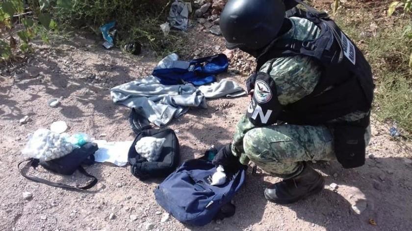 Un elemento de la Guardia Nacional recoge la droga que abandonó un hombre en la colonia Las Bellotas de Nogales.(Especial)