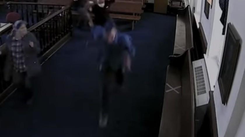 El hombre se escabulle de los oficiales y corre hacia la puerta de salida.(Captura de pantalla)