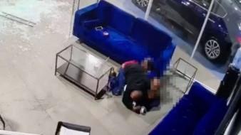 El hombre protege con su cuerpo a sus tres hijos menores que lo acompañaban en la sala de espera de la agencia de carros situada en el Bronx, NY.