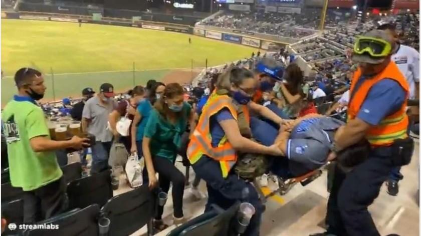 Luego del golpe la mujer, fue atendida por paramédicos, quienes la sacaron del estadio en camilla.(Especial)