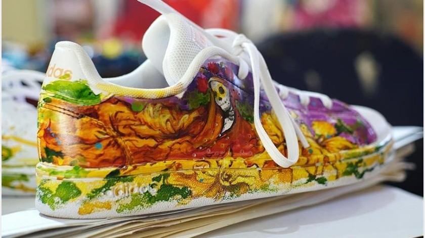 """Durante el breve lapso que toma el pincel para llegar de la paleta de colores al nuevo lienzo, Arellano va creando una de las imágenes de su nueva colección """"Día de Muertos"""" en zapatillas deportivas.(EFE)"""