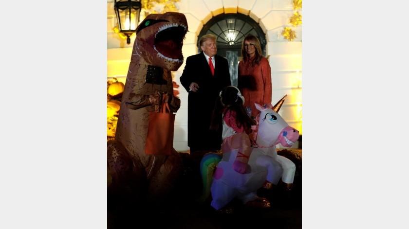 El presidente de los Estados Unidos, Donald J. Trump, y la primera dama Melania Trump saludan a los niños disfrazados durante un evento de Halloween en el jardín sur de la Casa Blanca en Washington, DC