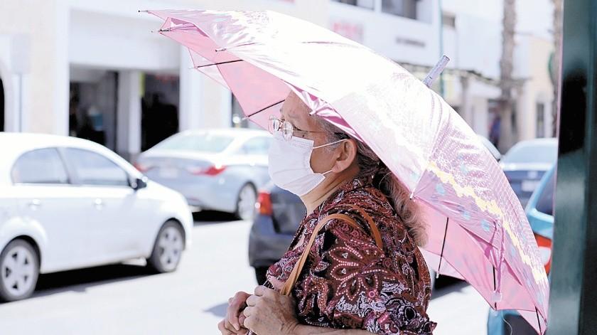 Una mujer no identificada porta una sombrilla como protección contra los rayos del Sol, pues hasta ayer el calor aún se sentía fuerte.(Julián Ortega)