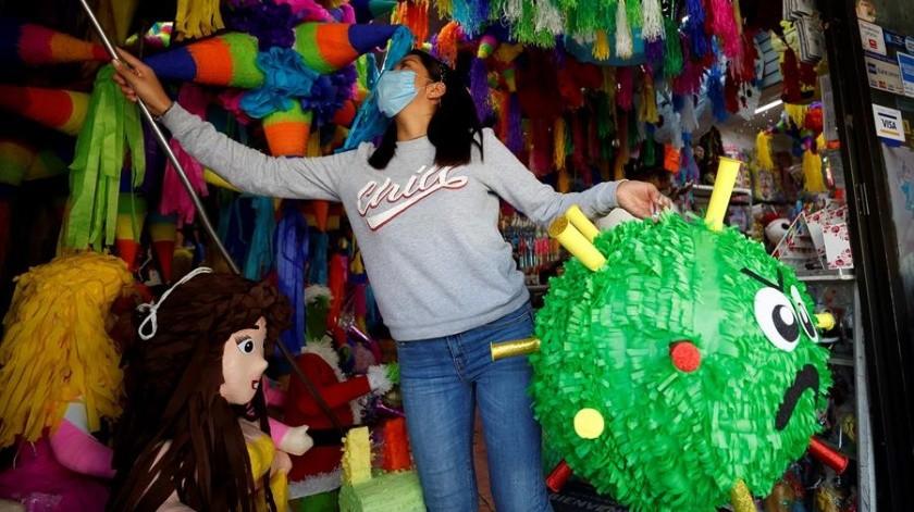 Una trabajadora sosteniendo una piñata alusiva al coronavirus en una venta de piñatas en la Ciudad de México.(EFE)