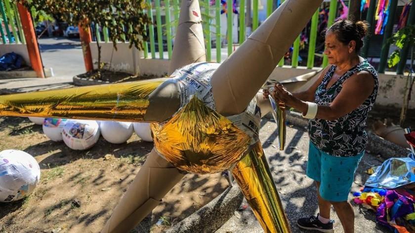 Una mujer en la elaboración de una piñata en el negocio de la familia Cornejo, quienes fabrican mas de 400 para ser entregadas a diferentes hoteles y ciudadanos en el puerto de Acapulco, Guerrero .(EFE)