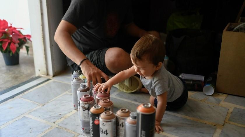 El artista callejero Wolfgang Salazar hace un inventario de sus pinturas en aerosol acompañado por su hijo Noah, en su casa en el barrio Petare de Caracas, Venezuela.(AP)