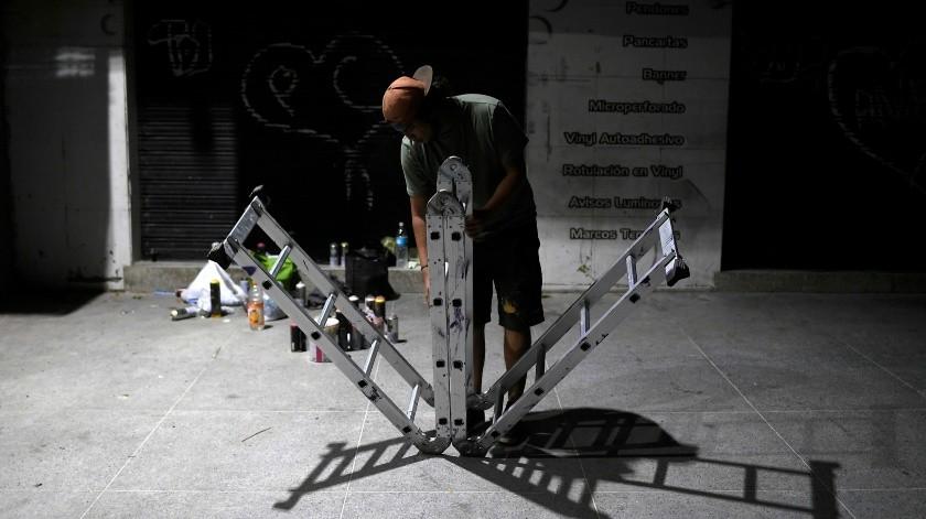 El artista callejero Wolfgang Salazar despliega una escalera portátil mientras trabaja en la noche en su mural más reciente en el barrio Boleita de Caracas, Venezuela.(AP)