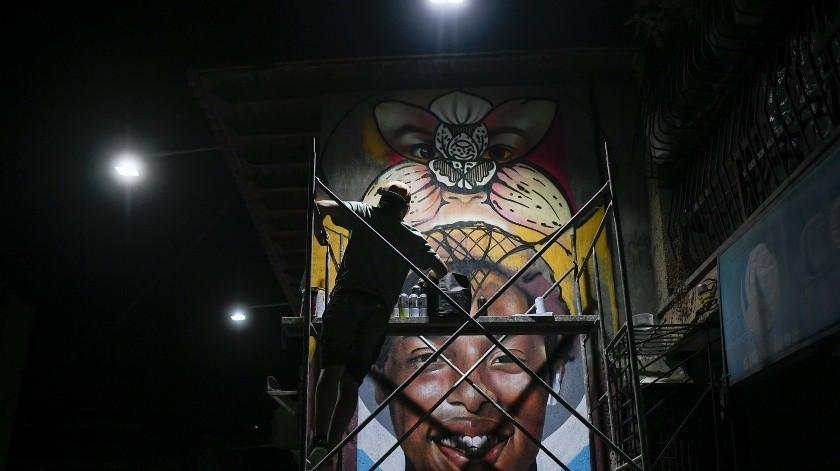 El artista callejero Wolfgang Salazar trabaja hasta altas horas de la noche en su mural más reciente en el barrio Boleita de Caracas, Venezuela.(AP)