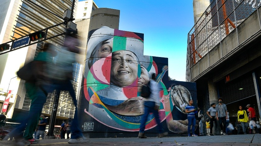 Los peatones pasan junto a un mural artístico con el cantante y actor Simón Díaz pintado por Wolfgang Salazar en el barrio Chacao de Caracas, Venezuela.(AP)