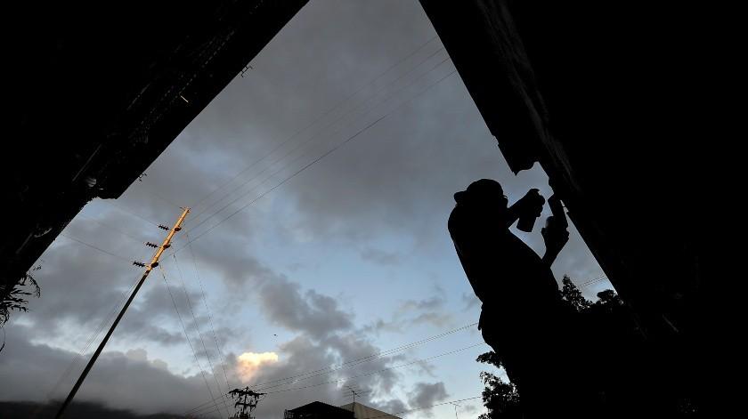 El artista callejero Wolfgang Salazar se recorta contra un cielo crepuscular mientras trabaja en su mural artístico más reciente, en el barrio Boleita de Caracas, Venezuela.(AP)