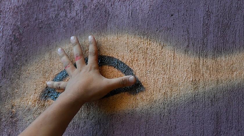 El artista callejero Wolfgang Salazar usa su mano para medir proporciones mientras comienza a pintar los ojos de su mural más reciente, en el barrio Boleita de Caracas, Venezuela.(AP)
