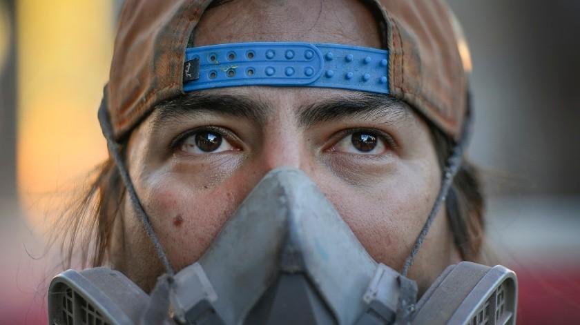 El artista callejero Wolfgang Salazar usa una máscara de pintor de seguridad mientras observa su mural más reciente en el barrio Boleita de Caracas, Venezuela.(AP)