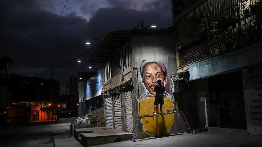 El artista callejero Wolfgang Salazar trabaja en su mural sobre el atleta venezolano Yulimar Rojas, en el barrio Boleita de Caracas, Venezuela.(AP)